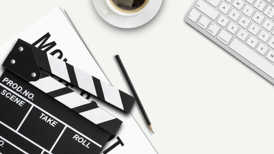 Movie clapperboard with pencil and computer keyboard and coffee