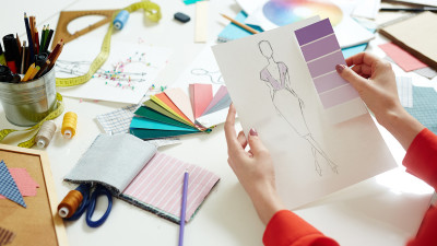 Fashion sketch with color swatches on desk