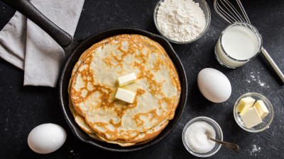 Crepes in cast iron skillet with ingredients