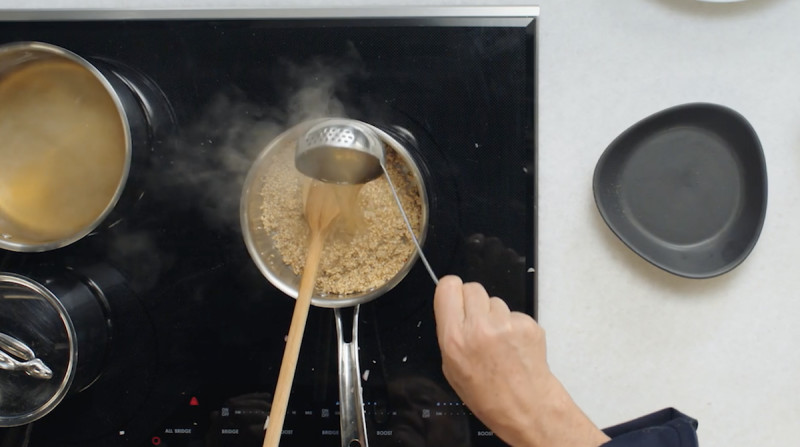 Wolfgang Puck pouring broth into oats on stove