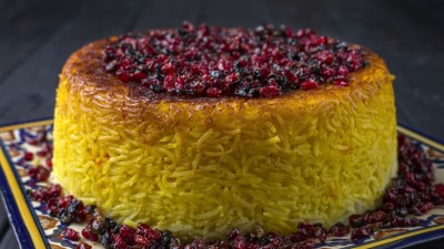 Tahdig Persian rice with berry topping on decorated plate