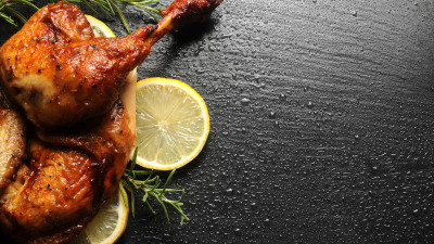 Roasted chicken thigh with lemon and rosemary on black background