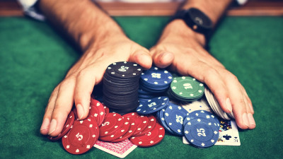 a person pushing poker chips on a table