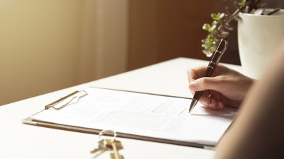 Person signing paperwork on clipboard with keys