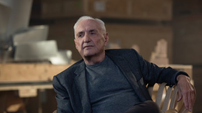 Frank Gehry in chair in front of designs