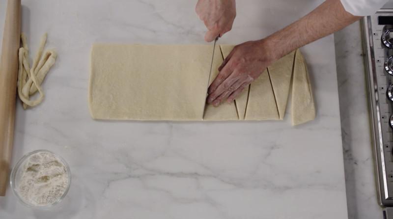 Dominique Ansel cutting croissant dough into triangles