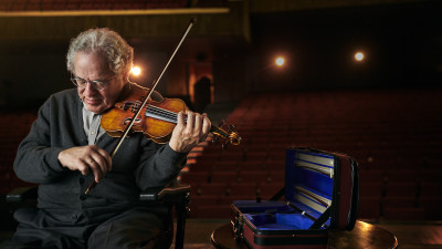Itzhak Perlman holding a violin on stage