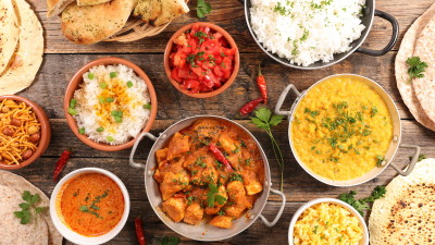 Indian food dishes in bowls on wood table