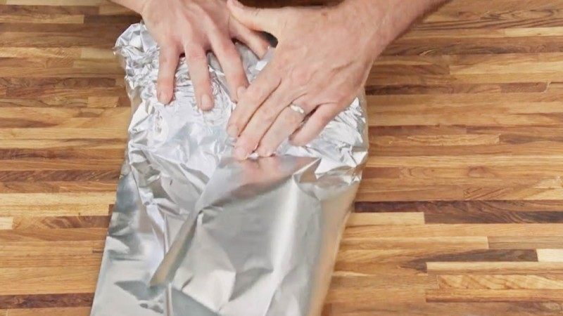 Aaron Franklin smoothing out tinfoil on wood table