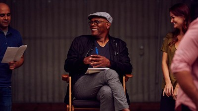 Samuel L. Jackson sitting in chair with people on set