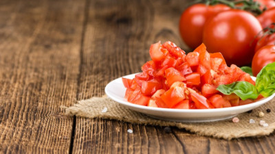 Diced tomatoes on plate with basil on dark wood