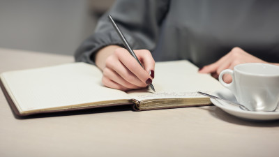 Girl writing in notebook with coffee