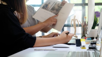 People working on a magazine together at desk