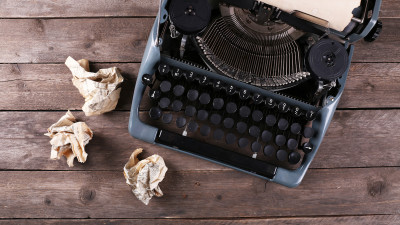 Vintage typewriter with tan crumpled paper on wood