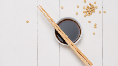 Soy sauce in small bowl with chopsticks