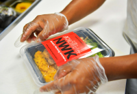 A close up look at gloved hands sealing a package that contains a Newark Working Kitchen meal. The NWK logo is prominent on the meal package's cover.