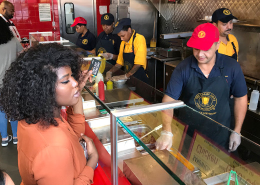 A woman in an orange shirt stands at a deli counter holding a Lunch Out Wednesday card. A restaurant employee in a red cap is serving her.