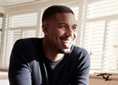Actor and Newark native Michael B. Jordan is seen smiling while looking off in the distance, as if in conversation with someone off camera. He is wearing a blue crew neck sweater and behind him, light filters through the slats in blinds covering a wall of windows in a living room.
