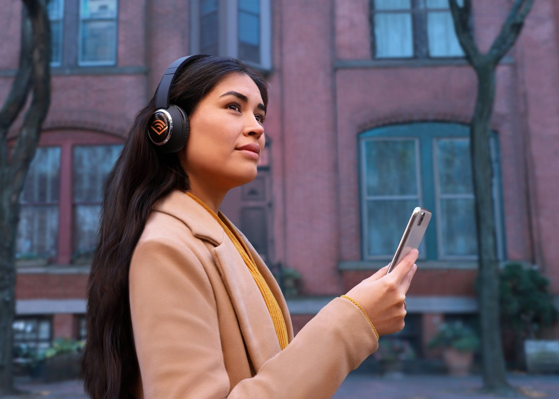 Woman listens to Audible on a street in Newark