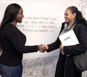 Two women shake hands in front a whiteboard in a conference room. One holds an Audible folder tucked under her arm.