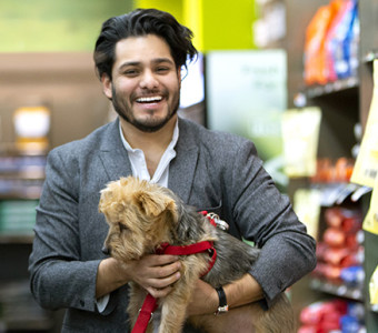 A man in a blazer carrying a small terrier with a red leash walks through a pet store in Newark.