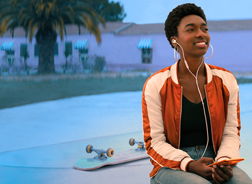 A young person listens to Audible outside with skateboard behind them.