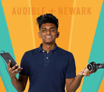 A high school student in a blue polo shirt stands with a tablet in one hand and a pair of headphones in the other. Audible + Newark is displayed behind him.