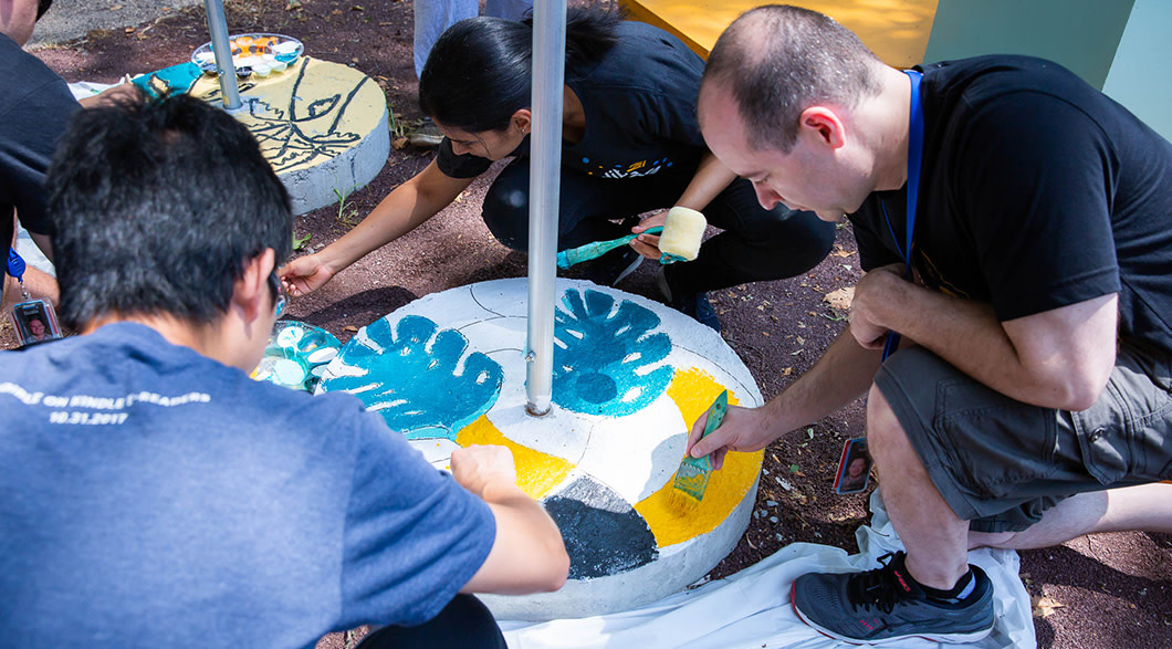 Several Audible employees and Newark artists paint leaves and other designs on the cement based of solar lights.