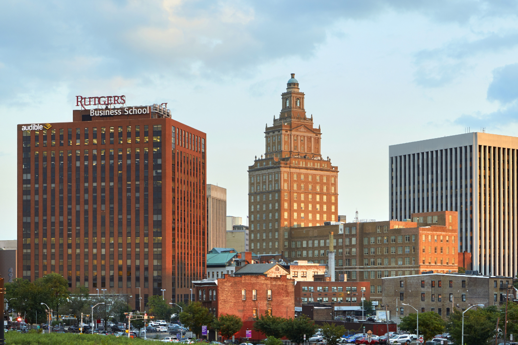 The Newark skyline appears at dusk as the light turns golden on the red brick buildings. The sky is blue with wisps of clouds. Two of Audible's office buildings appear in the foreground.