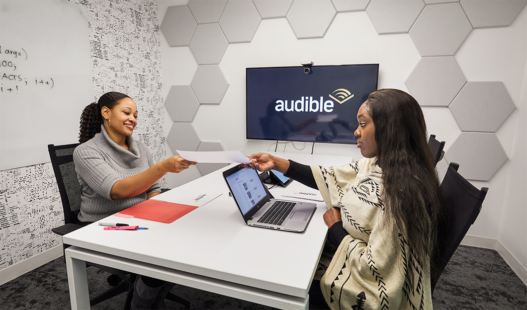 Two women meet in an Audible conference.