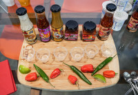 Several hot sauces and chilis line a cutting board with tasting cups in the middle.