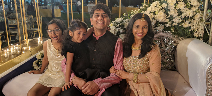 Jai sits on a couch with his wife and two daughters.