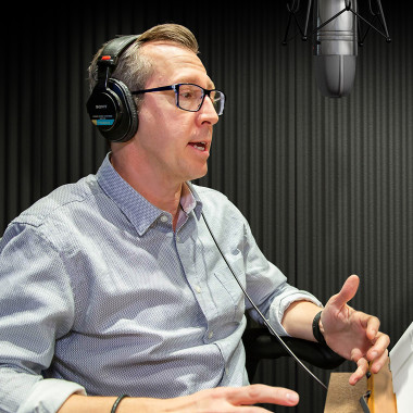 Bob Carrigan sits in a audio studio recording a message to Audible employees