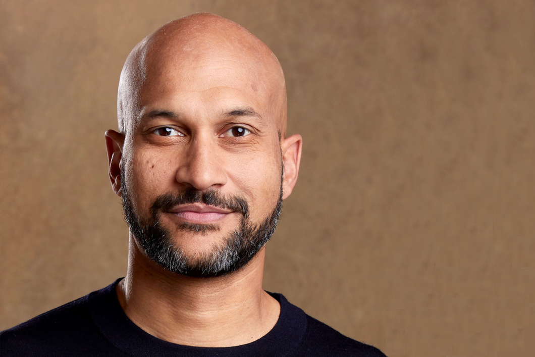 Close headshot of Keegan-Michael Key with a shaved head, mustache and beard and wearing a black shirt against a beige background.