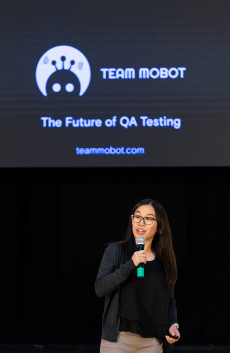 The founder of Team Mobot, a tech start-up, presenting her company with the logo on a screen behind her.