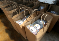 Brown paper bags with handles sit set up in a row and filled full of meals packaged in plastic containers with NWK logos on them.
