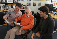 Stan Lee sits in front of a microphone reviewing text with two collaborators