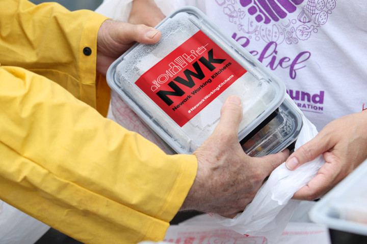 A Newark Working Kitchens meal is seem being handed off from one person to another via a close up shot on the meal container and the hands holding and receiving it.