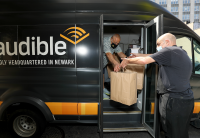 A man in a delivery van, with an Audible logo on the side, hands two large paper bags full of Newark Working Kitchen meals out the van door to a man standing on the street.