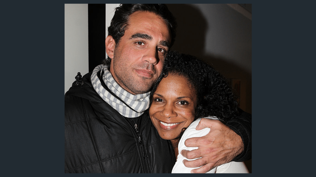 Actor Bobby Cannavale stands with his arm around actor Audra McDonald, holding her close. She is smiling and they are both looking directly into the camera. He is wearing a black zip up jacket with a gray and white scarf wrapped around his neck. She has on a white long sleeve shirt.