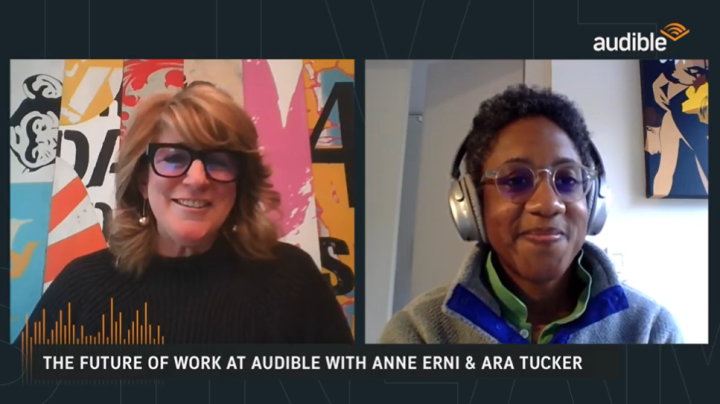 "The two speakers from the LinkedIn Live conversation are showcased in their homes. Anne Erni, set on the left, is sitting in front of bright colored street-inspired artwork wearing a black shirt and black framed glasses. Ara Tucker, set to the right, is sitting in front of a white wall with artwork in the background and wearing silver headphones, a grey sweater and clear glasses. The Audible logo is placed on the top right corner, and the title of the livestream ""The Future of Work at Audible"" with Anne Erni and Ara Tucker is displayed on the bottom."
