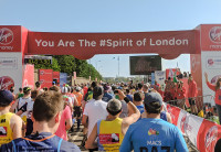 A crowd of runners going through the starting gate at the Virgin Money London Marathon