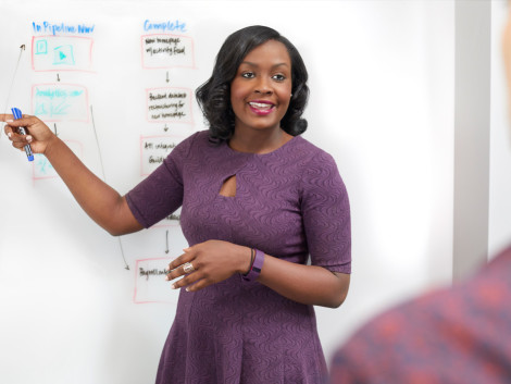 Isa Watson, the founder of a tech startup, presenting a flowchart on a whiteboard.