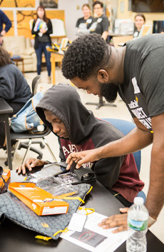 An Audible employee assists a high school student, seated at a table, with setting up his tablet to listen to Audible as part of Project Listen Up.