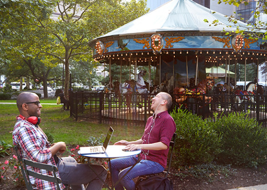 Two men work on computers at a table in a park in Newark with their headphones on. A carousel is behind them.