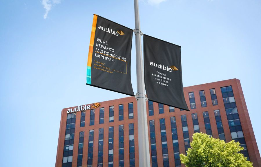 Two Audible banners hang on a light pole in front of a large maroon building with Audible's logo on the side.