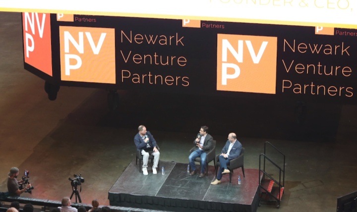 Three people sit on stage for a panel discussion under a large Newark Venture Partners sign.