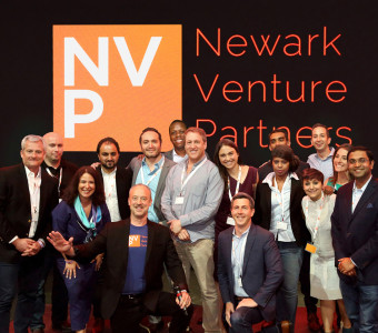 A group of tech start up founders standing in front of the Newark Venture Partners logo.