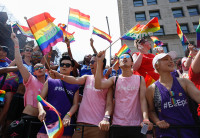 People crowded together to watch the NYC Pride March. They're wearing pink and purple #BeEpic shirts and waving rainbow-colored Pride flags.