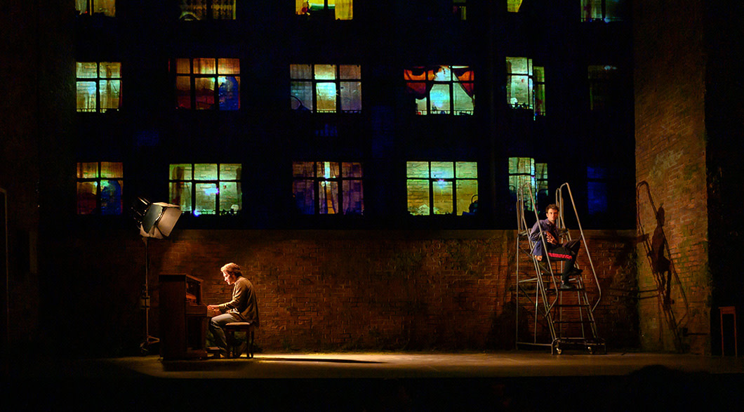 On a theatre stage, Jake Gyllenhaal sits playing a piano downstage right with a large light on him while Tom Sturridge sits on a rolling ladder upstage left looking out at the audience. An image is projected on the wall behind them to make it look like an apartment building with lots of lit windows framed by curtains.